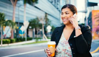 woman holding coffee talking on her phone walking outside